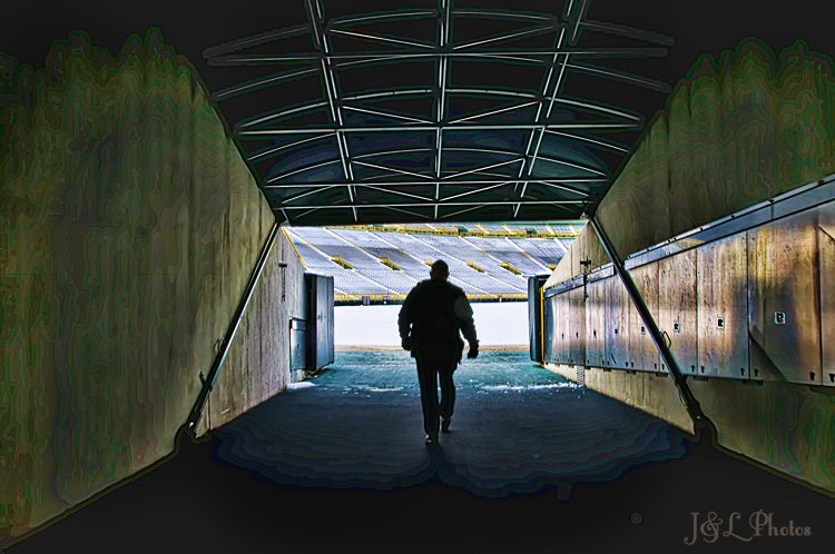 a lone stadium employee enters the green bay packers lambeau field via the visitor players tunnel